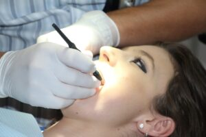 Woman getting teeth cleaning from dentist in Katy TX